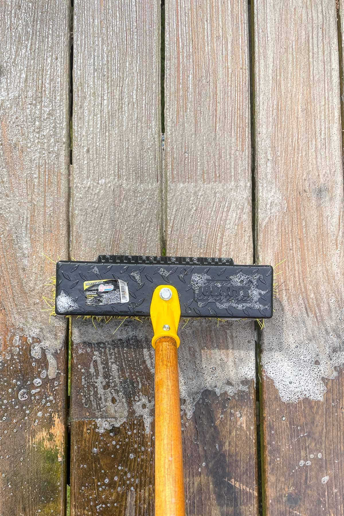 cleaning the surface of a deck with deck cleaner and a scrub brush