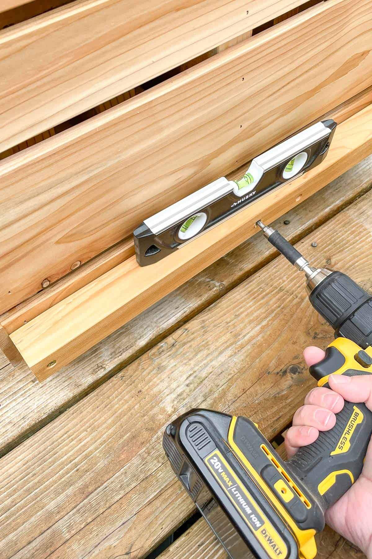 attaching the bottom plant shelf support with a drill and a level