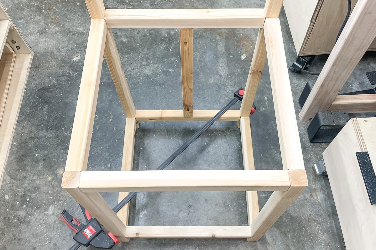 clamp the opposing corners to force the frame into square while the glue dries