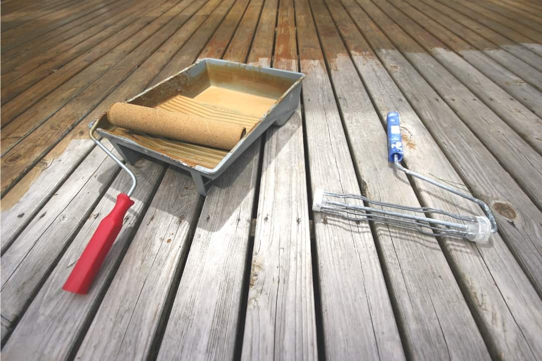 applying deck stain with a roller
