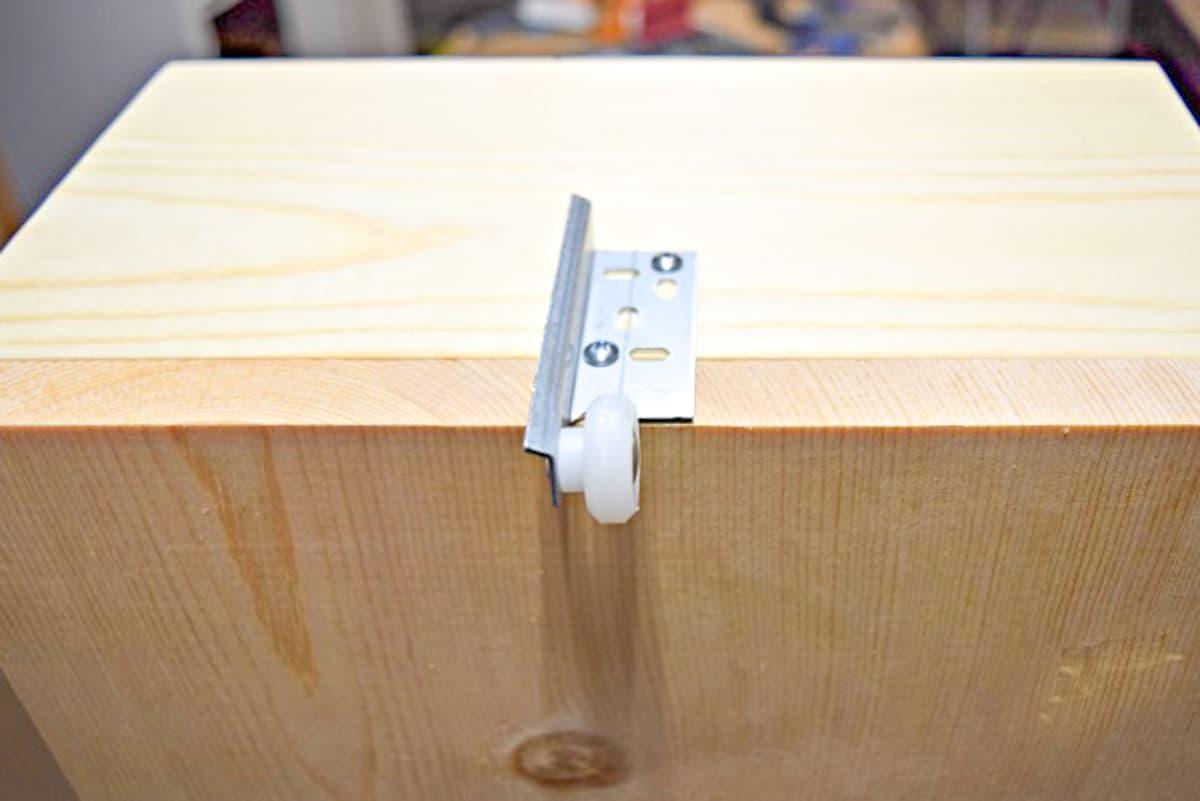 center mount drawer slide wheel attached to back of trash can cabinet drawer