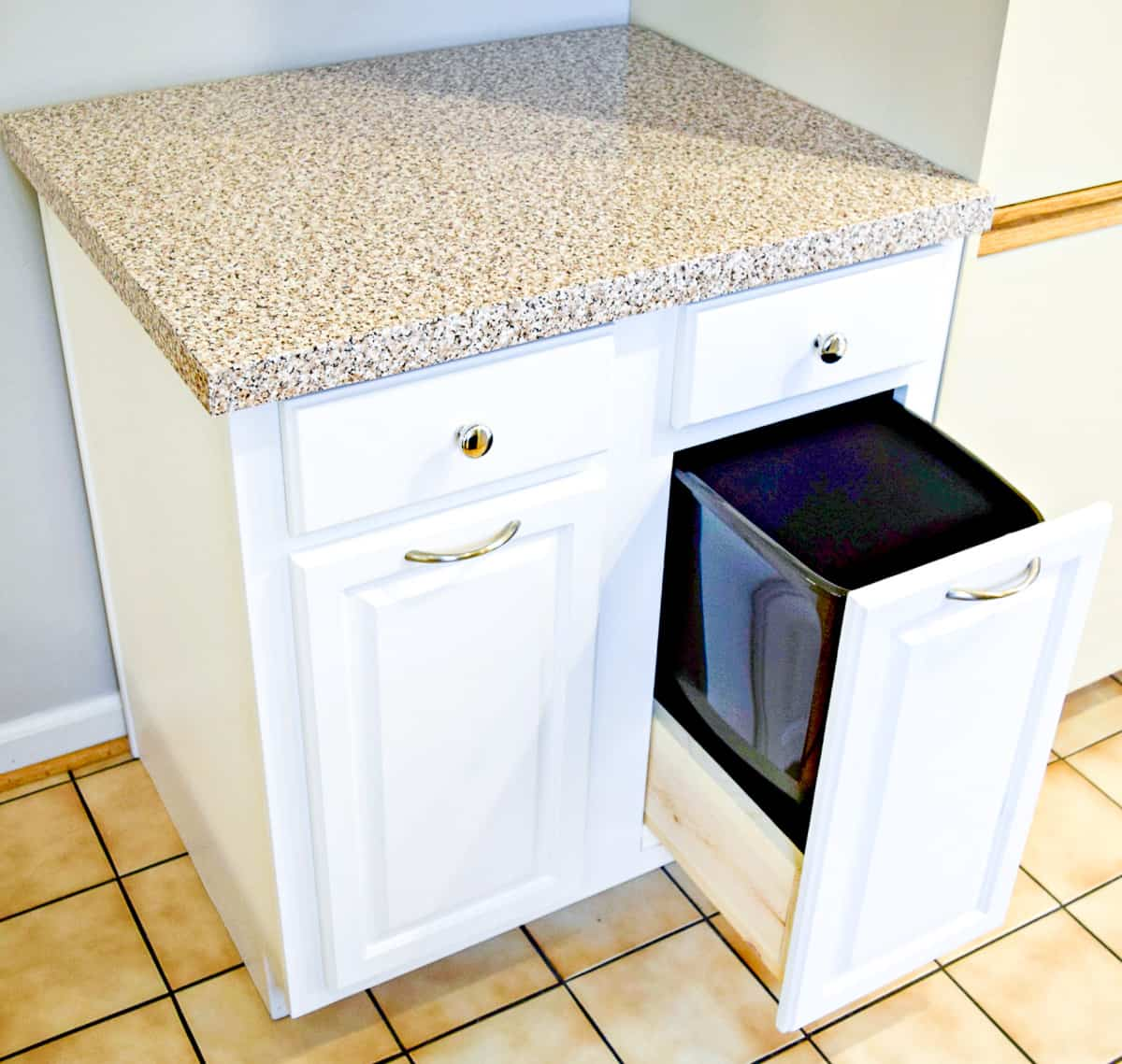 used kitchen cabinet converted to a trash can cabinet