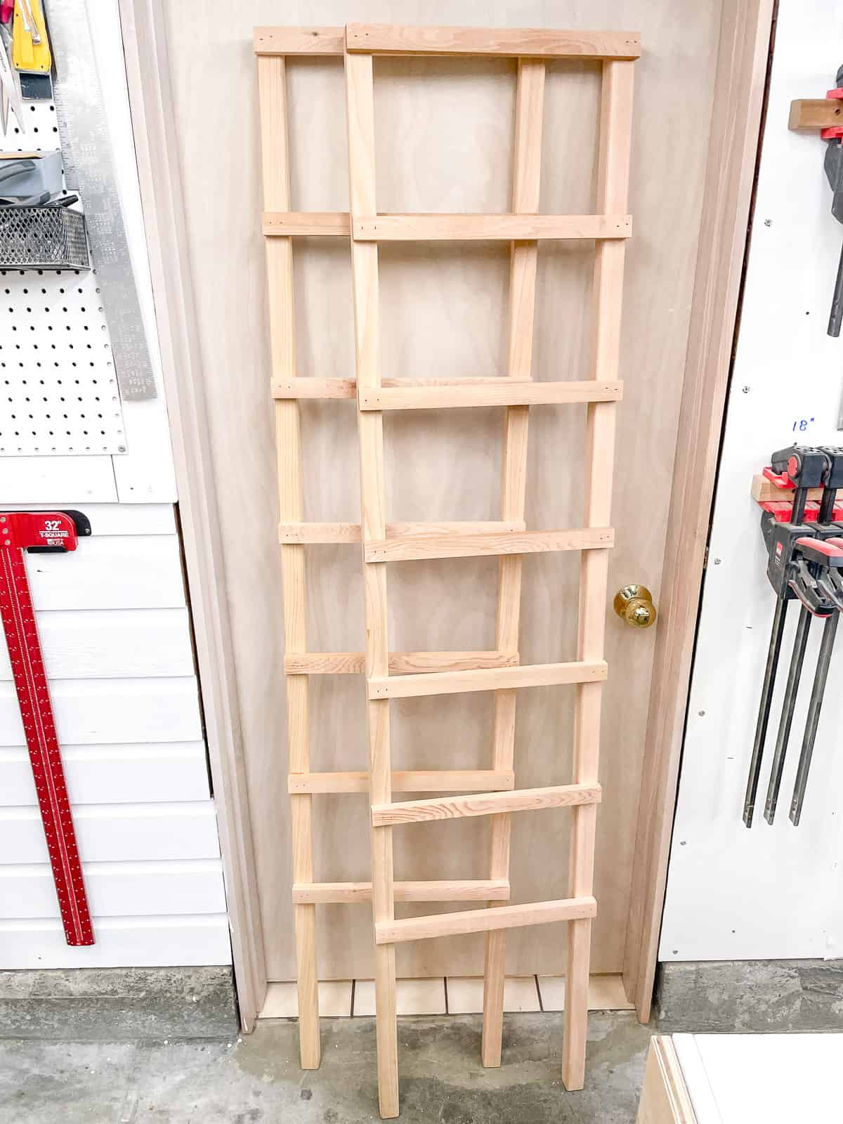 legs of homemade tomato cage assembled and leaning against door