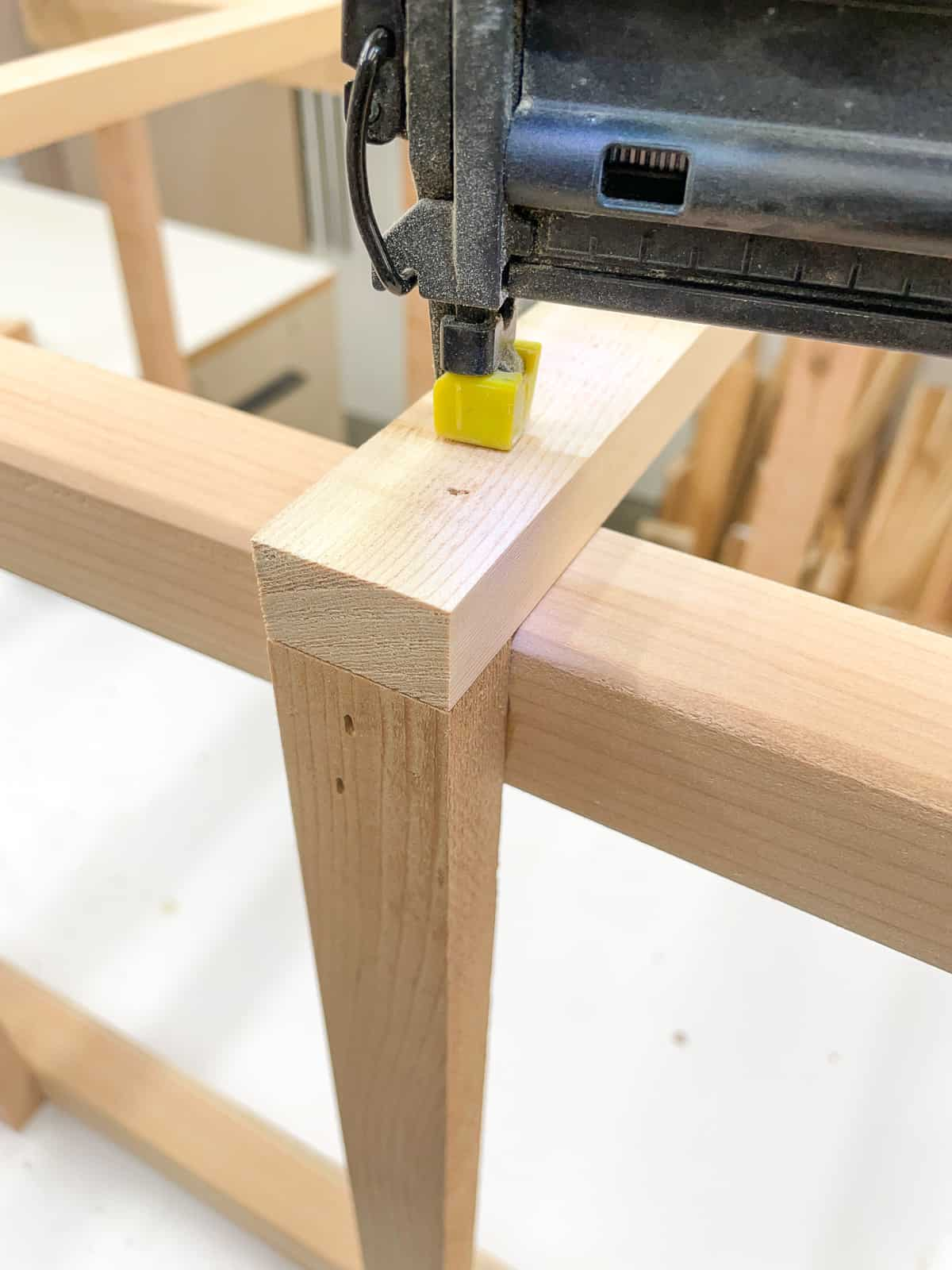 attaching slats to a wooden tomato cage with a brad nailer