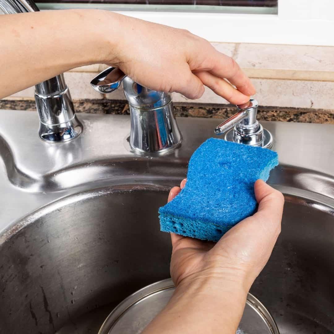 using a kitchen sink soap dispenser for dish soap on a sponge
