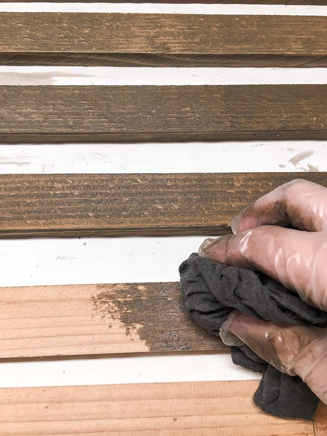 staining slats for the trellis with a rag