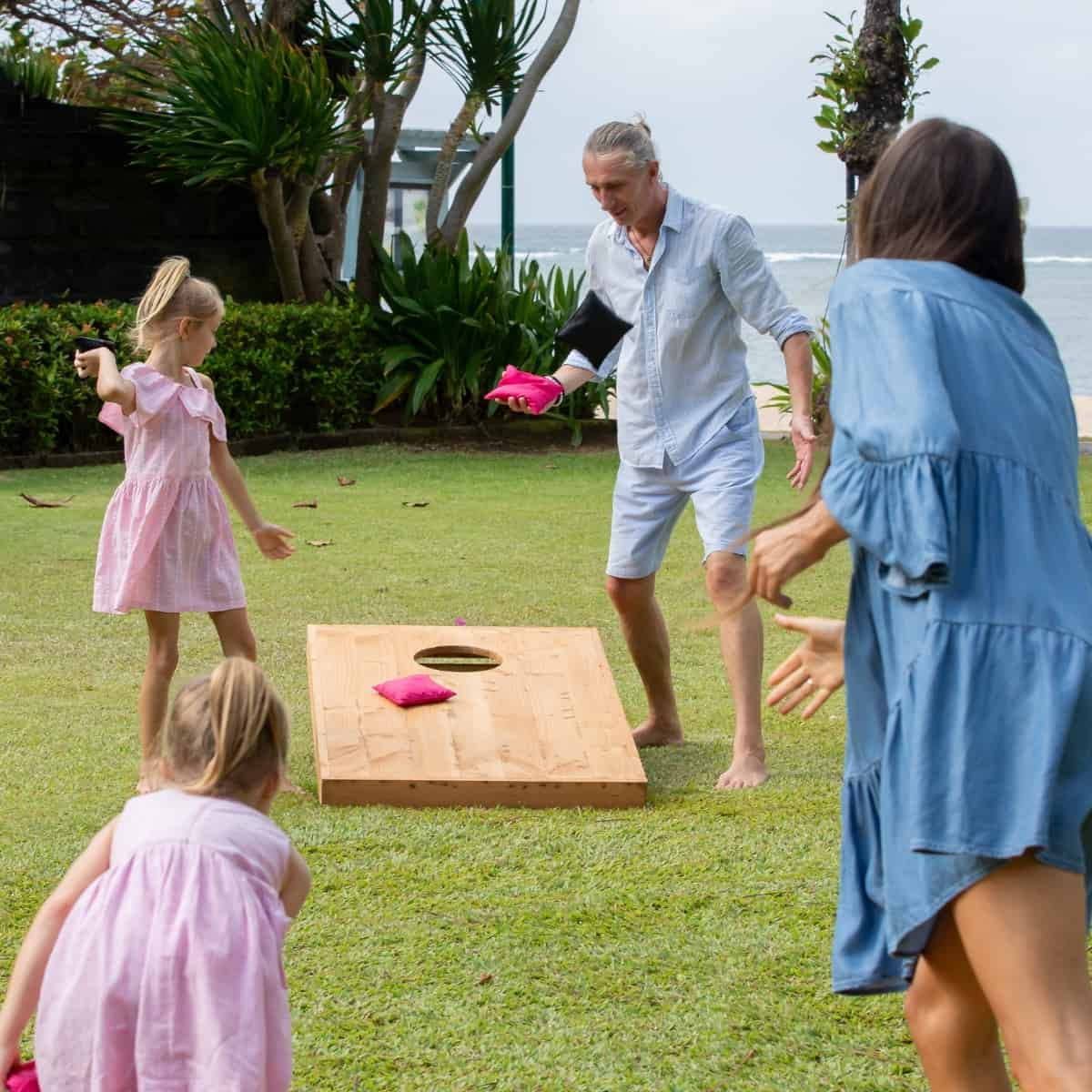 family playing cornhole at the beach