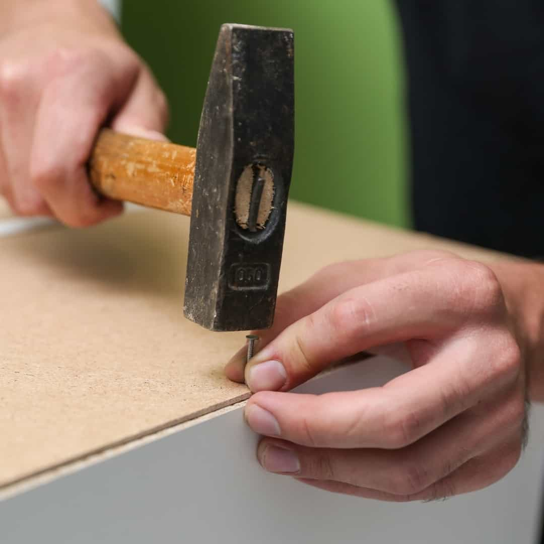attaching cabinet back panel with a hammer and panel nails