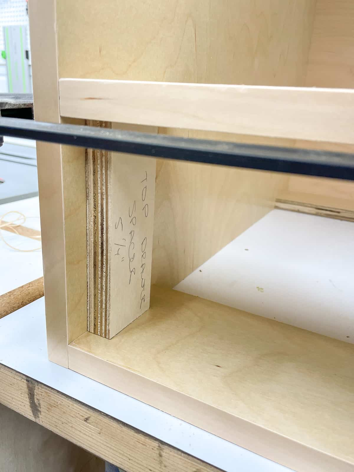 using a spacer to attach the drawer support for the cabinet box at the correct height