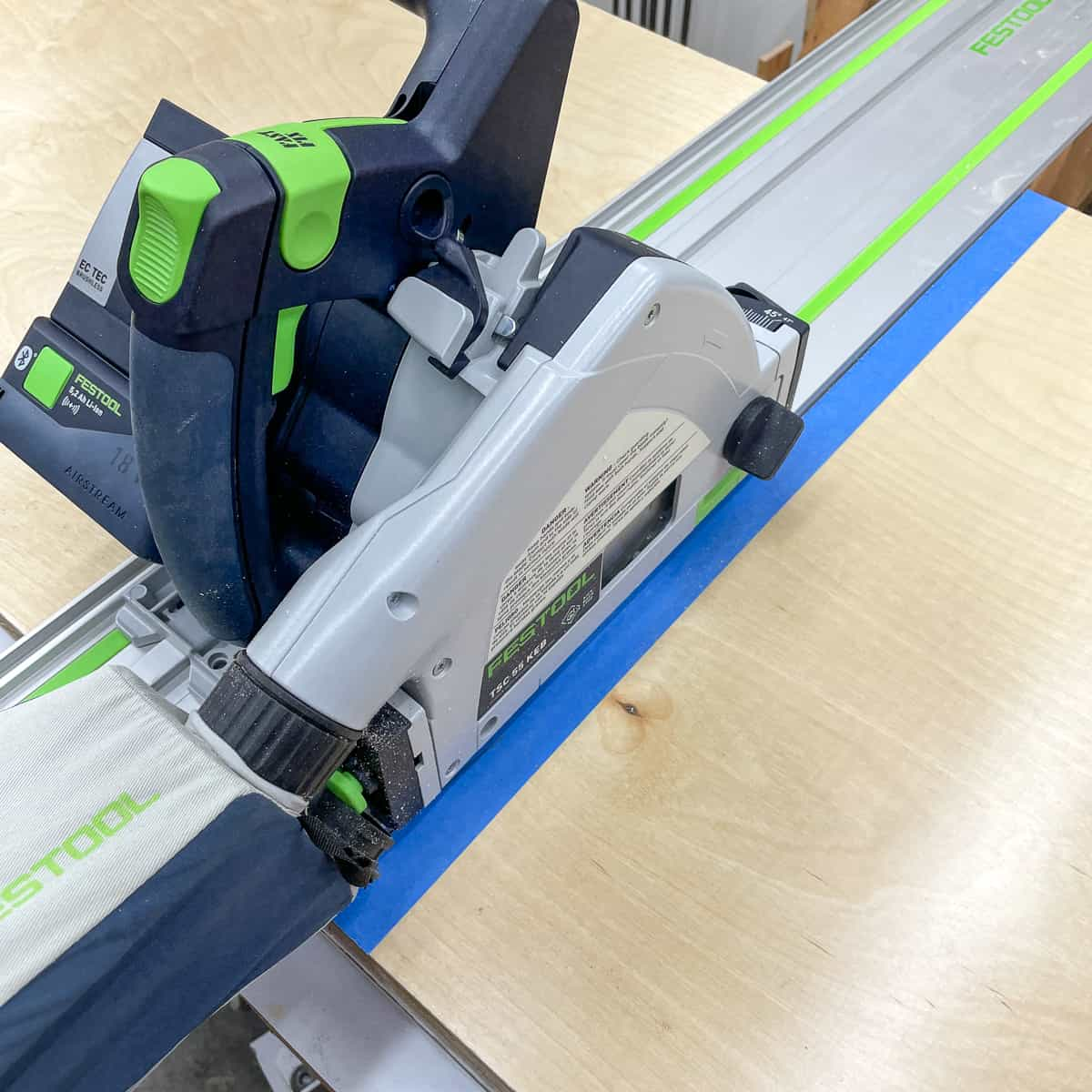 cutting plywood pieces for cabinet box with a track saw with blue painter's tape along the cut line