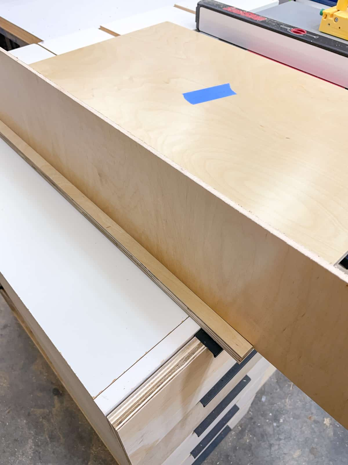 testing fit of back panel inside groove of the side piece of the cabinet