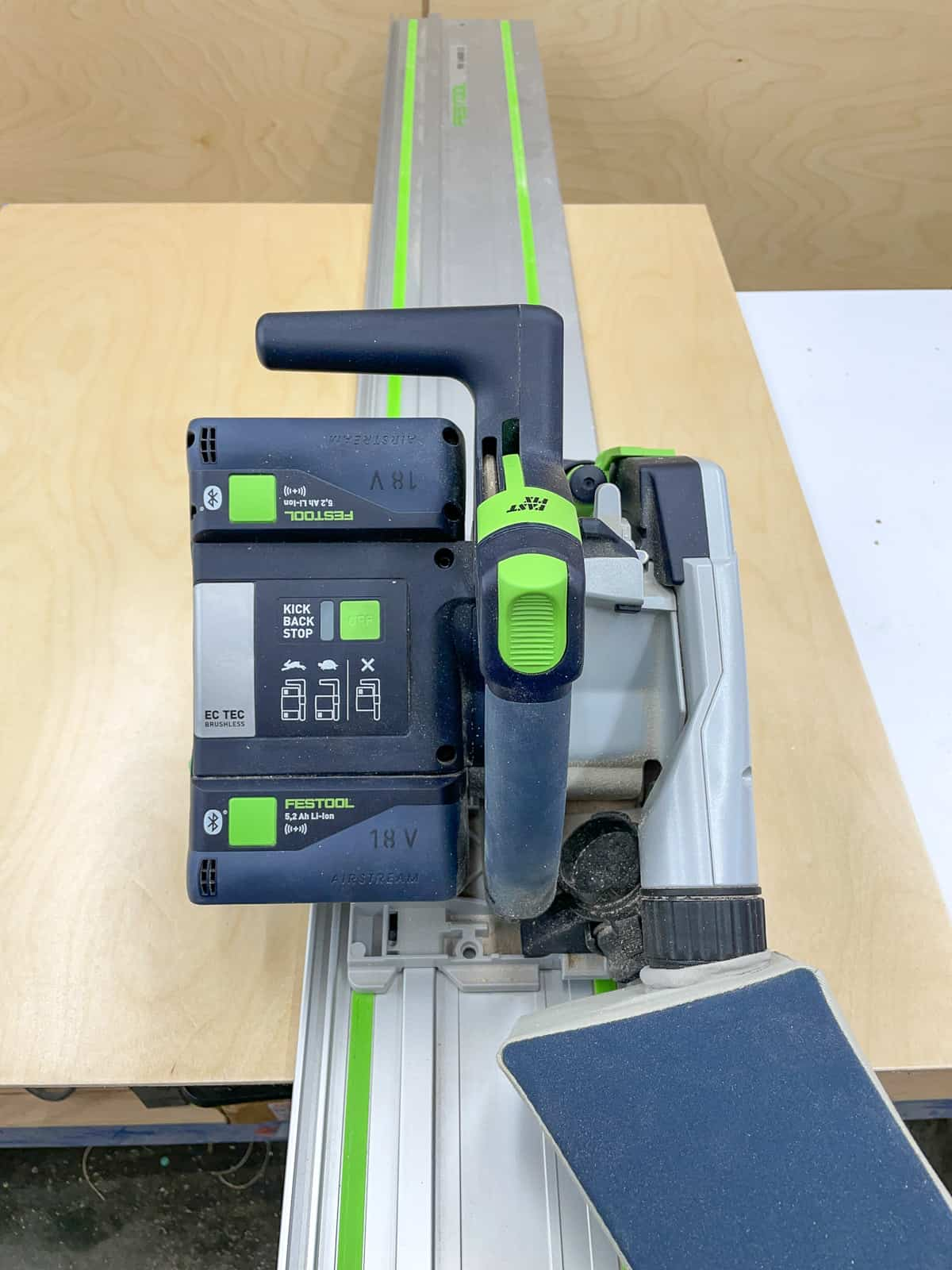 Festool track saw with track on plywood sheet before cutting cabinet box pieces
