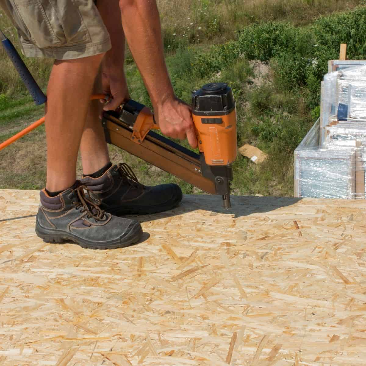 construction worker nailing OSB sheet to flooring joists