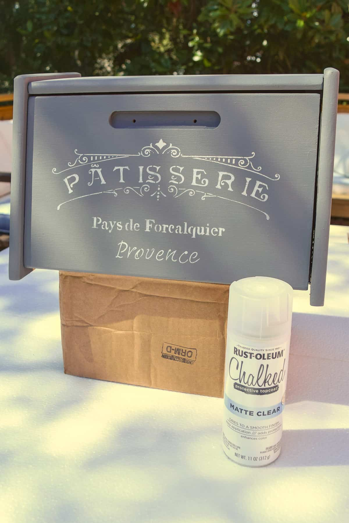 applying a spray top coat to painted bread box outdoors