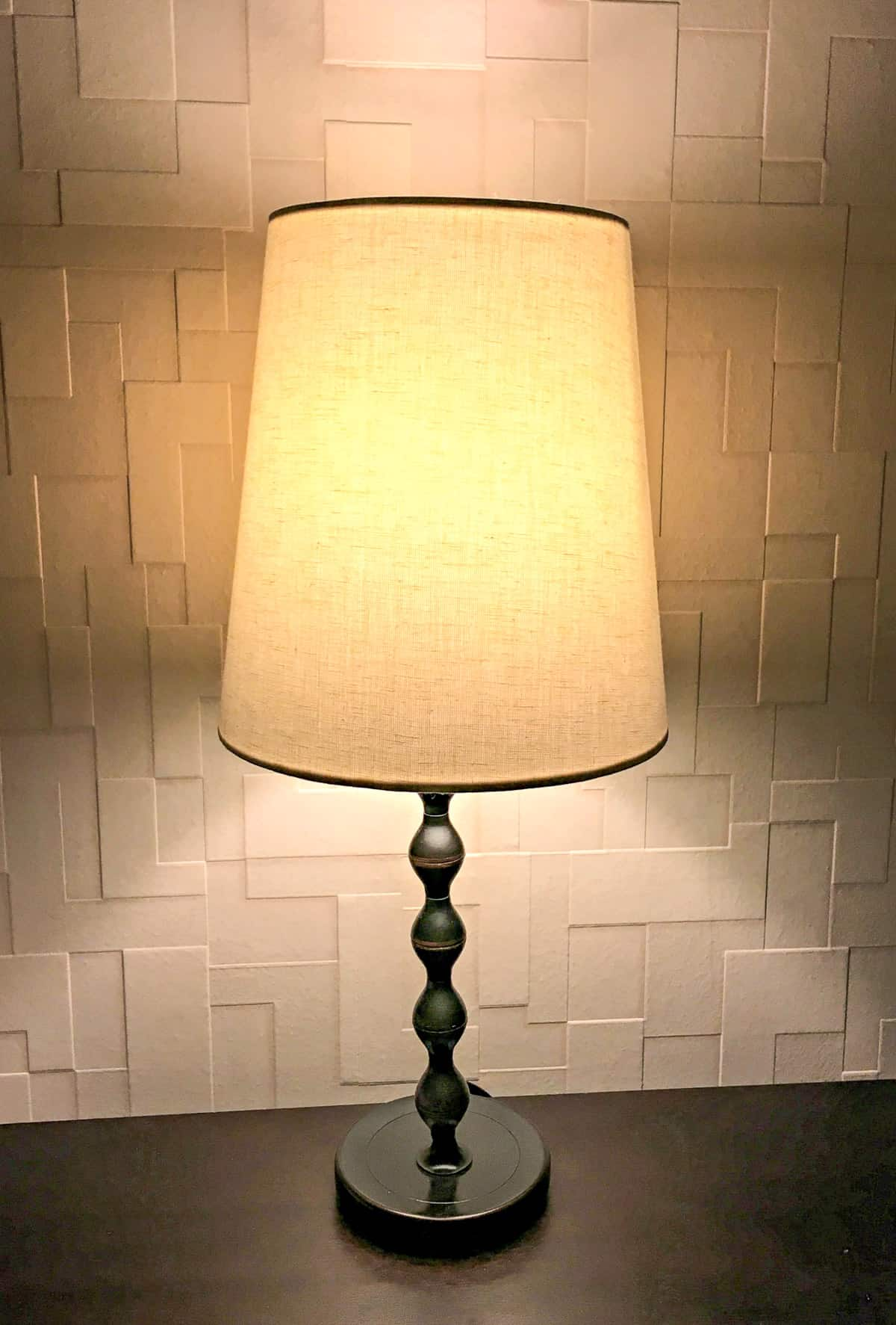 bedside lamp in front of textured wallpaper accent wall