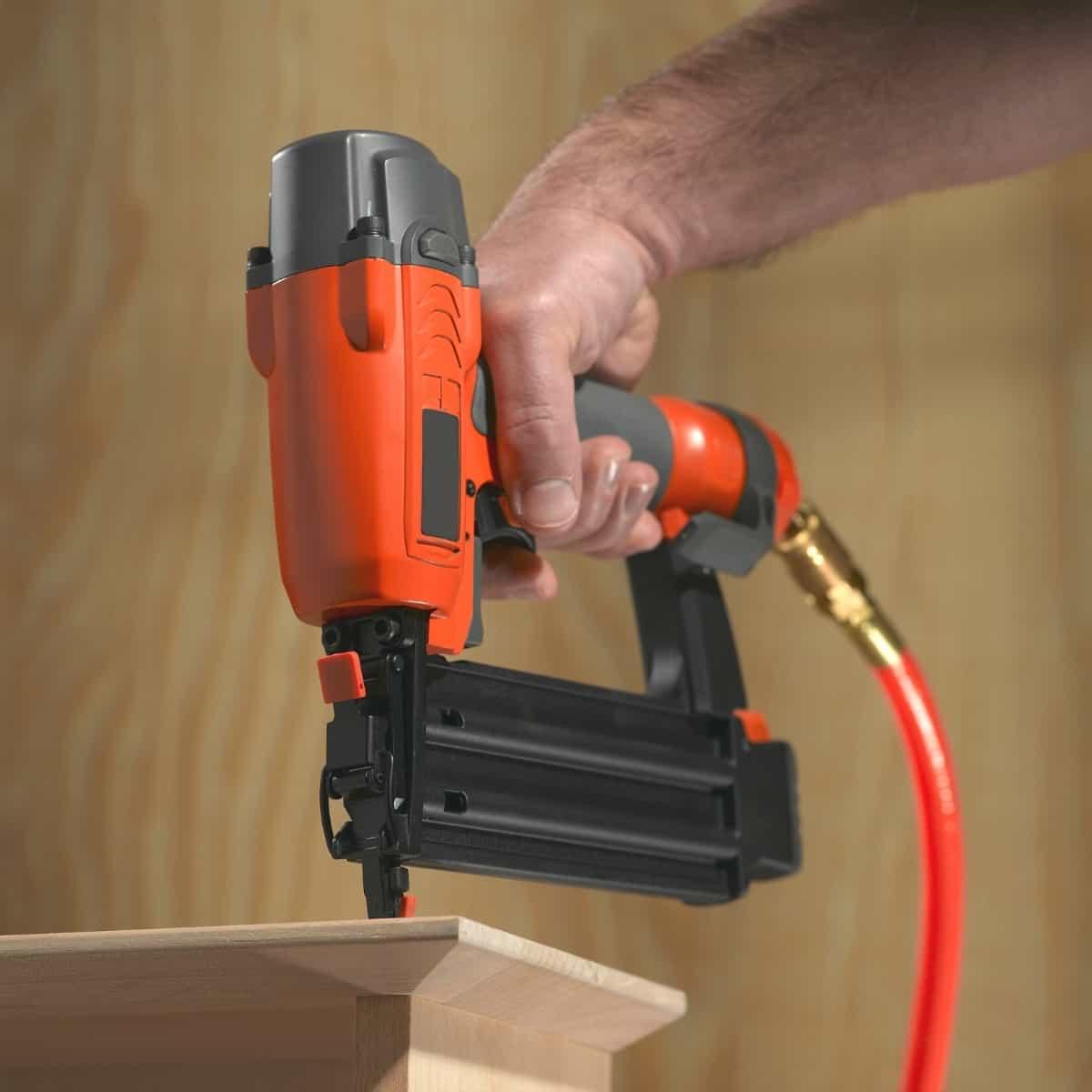 finish nailer attaching hardwood trim to cabinet